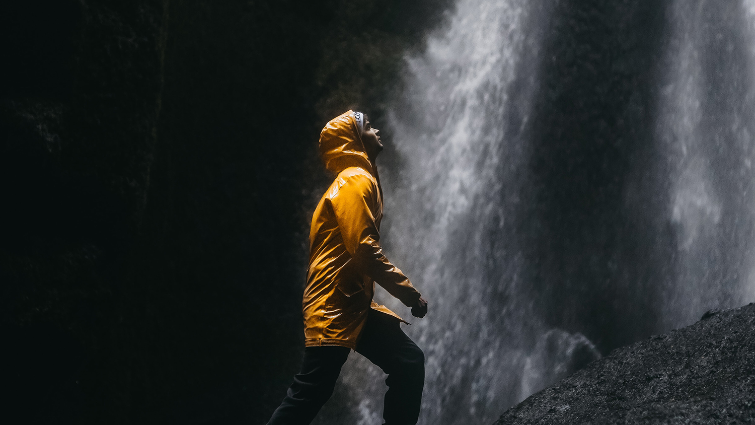 young man looking up at a waterfall in darkness