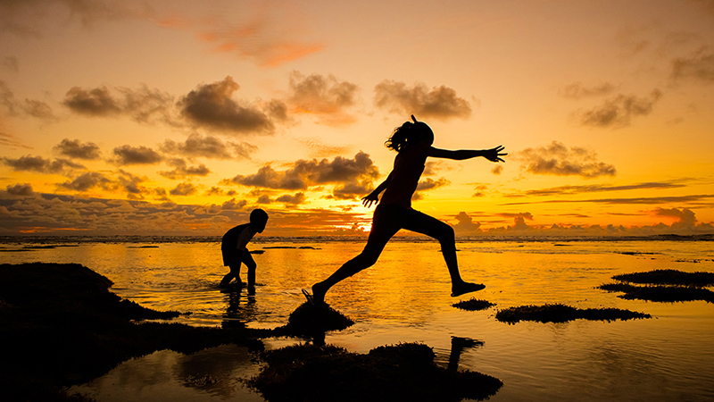 children leaping on the sea shore